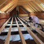 Aplikátor izolace izolace při práci během zateplování podlahy domu ve Hvozdnu